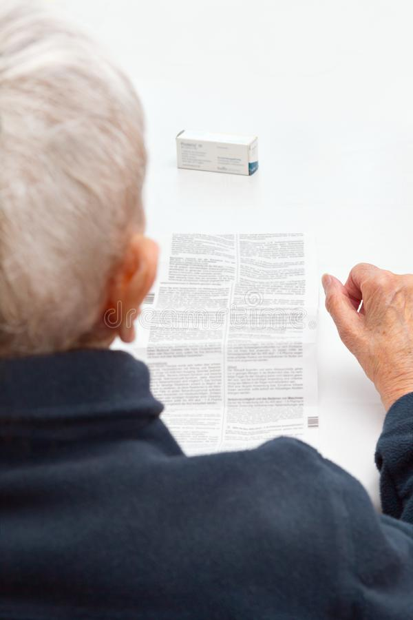 Old woman unable to read drug package leaflet. Old woman sitting at a table in her living room unable to read the information sheet of her prescribed medicine stock images