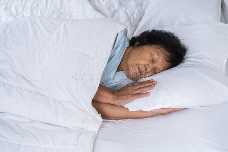 Old woman sleeping on a bed. In bedroom royalty free stock image