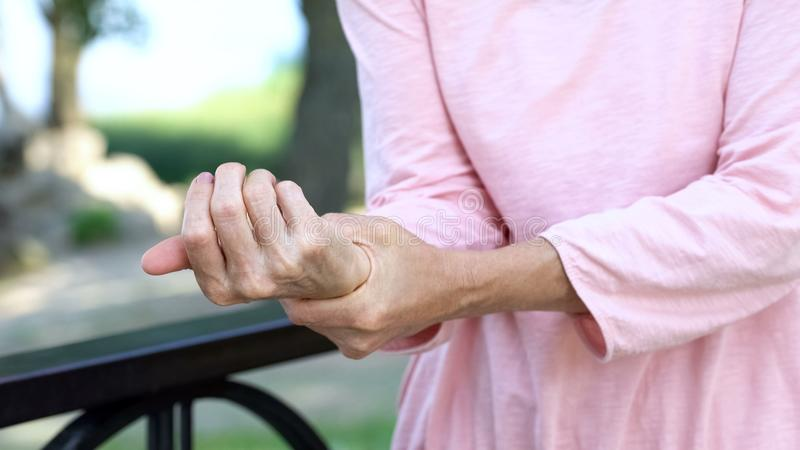 Old woman stretching numb arm, weakness of muscles in senior age, arthritis. Stock photo royalty free stock image
