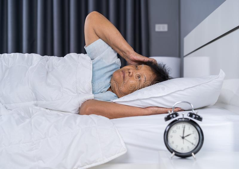 Old woman suffering from insomnia is trying to sleep in bed stock image