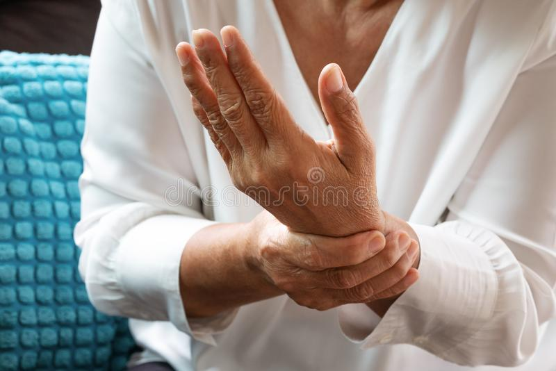 Old woman suffering from wrist hand pain, health problem concept royalty free stock images