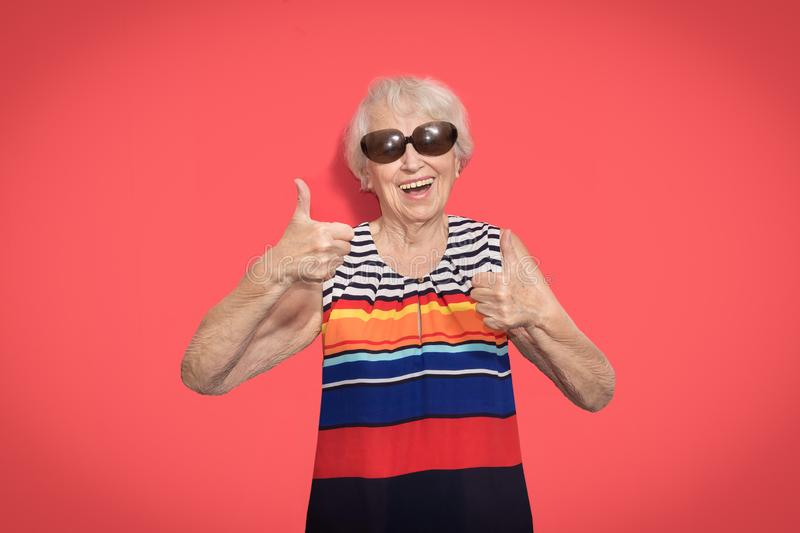 Old Woman with surprised expression on her face. Old smiling woman with surprised expression on her face on red studio background. Human emotions concept stock photography