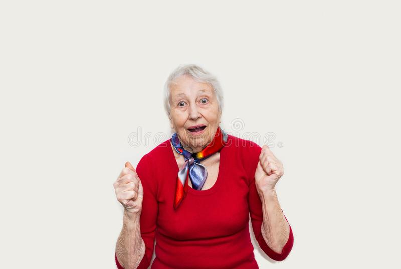 Old Woman with surprised expression on her face. On white studio background. Human emotions concept. Positive emotional old lady standing indoor royalty free stock images