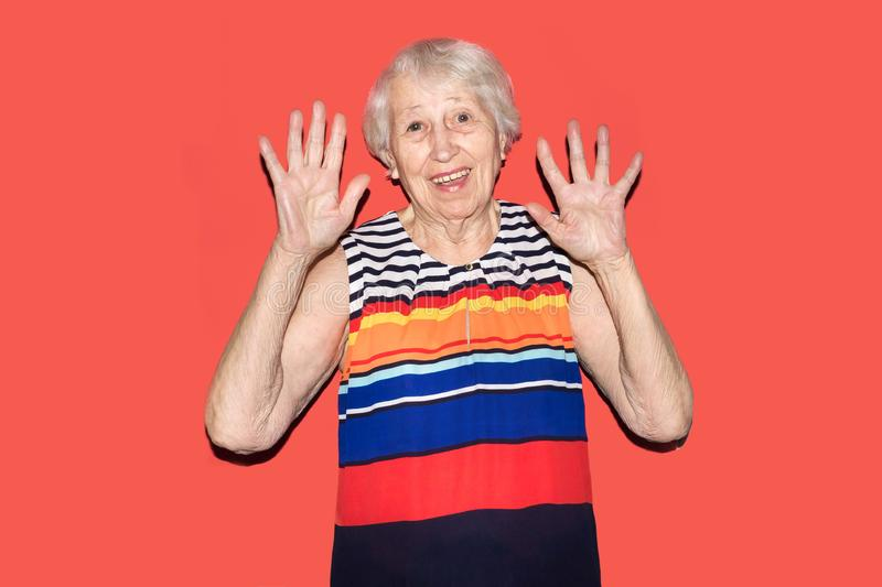 Old Woman with surprised expression on her face. Old smiling woman with surprised expression on her face on red studio background. Human emotions concept stock photos