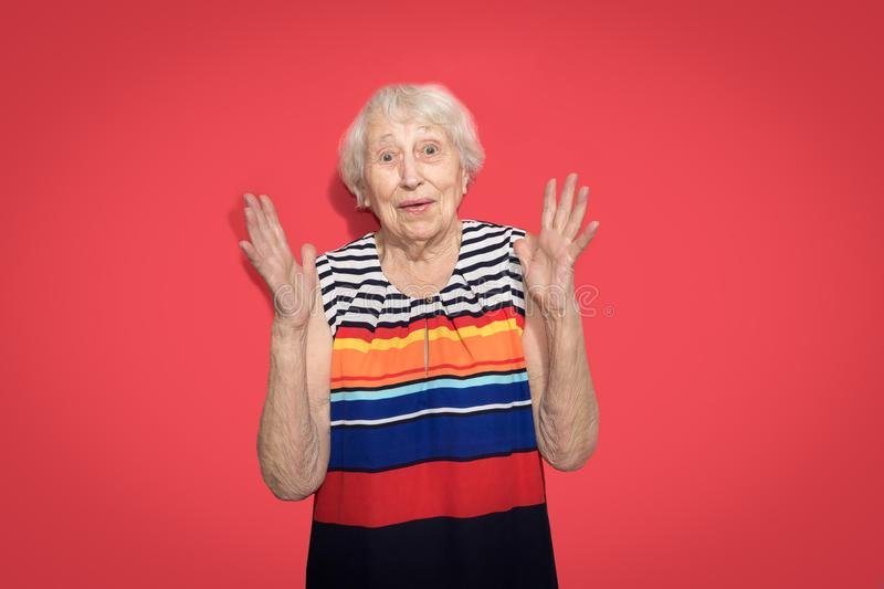 Old Woman with surprised expression on her face. Old smiling woman with surprised expression on her face on red studio background. Human emotions concept royalty free stock image