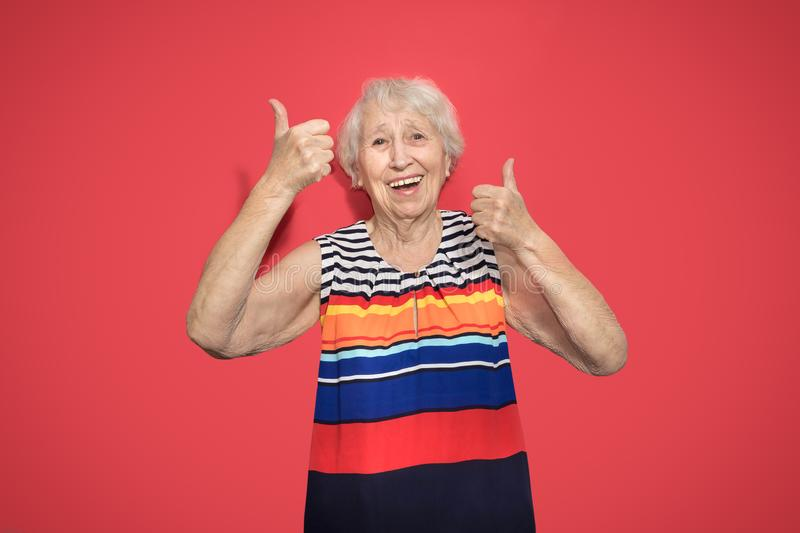 Old Woman with surprised expression on her face. Old smiling woman with surprised expression on her face on red studio background. Human emotions concept stock photo