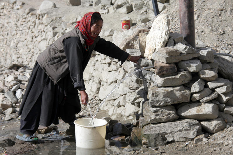 Old woman taking water from a well royalty free stock image