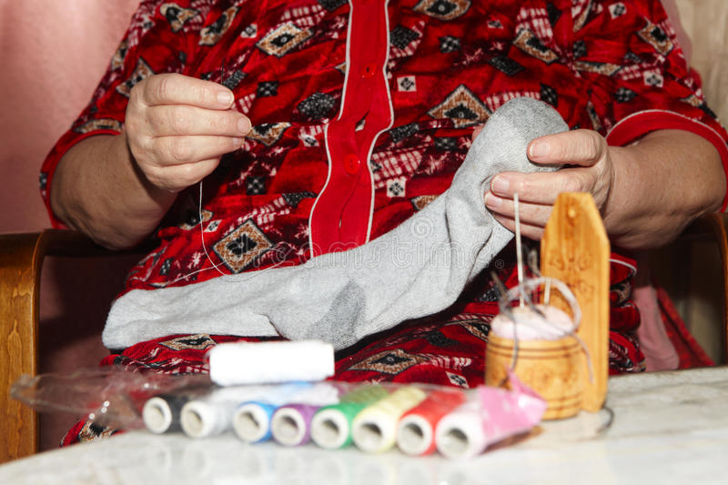 Old woman to sew over a tear stock photos