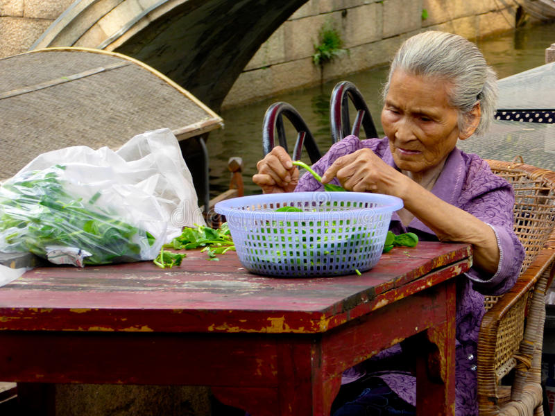 Old woman triming vegetables for cooking stock images