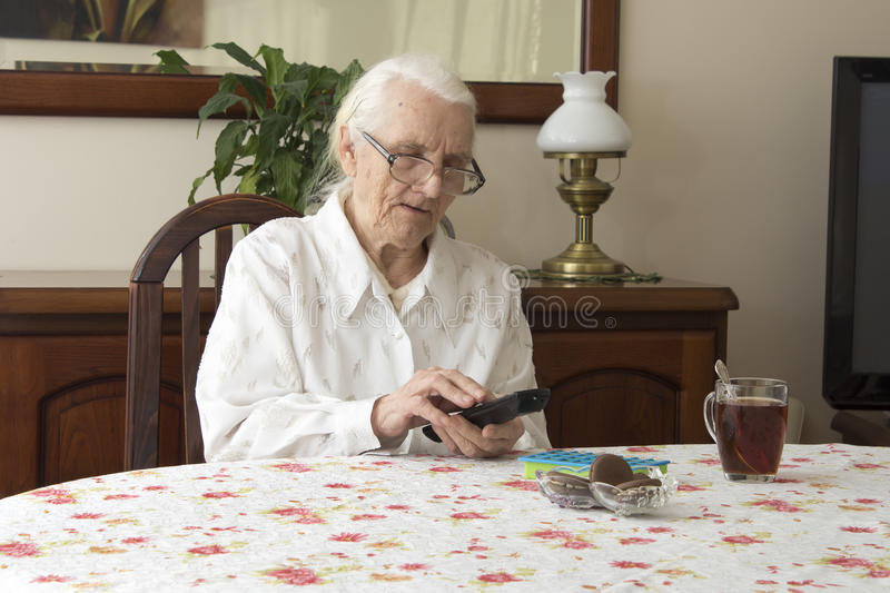 The old woman turns on the TV remote control sitting at the table. stock photos