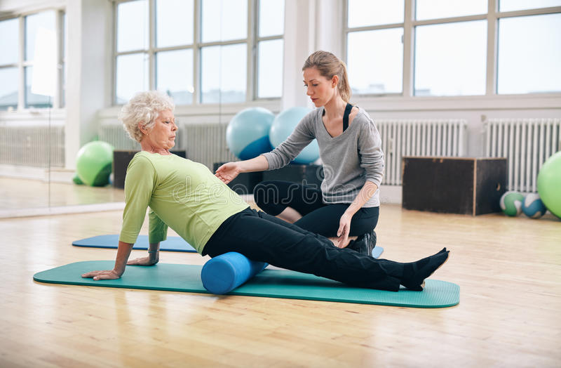 Old woman using foam roller with personal trainer royalty free stock images