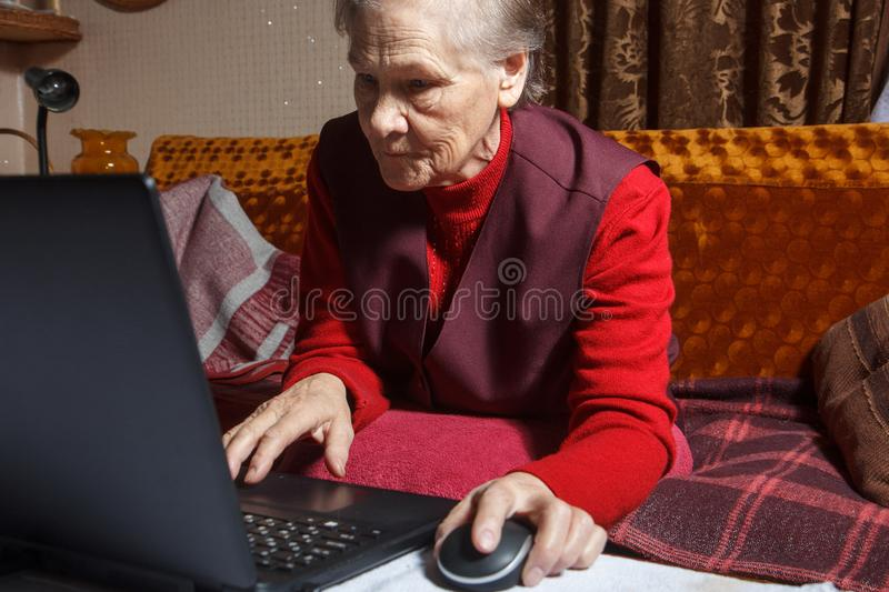 Old woman using laptop stock photos