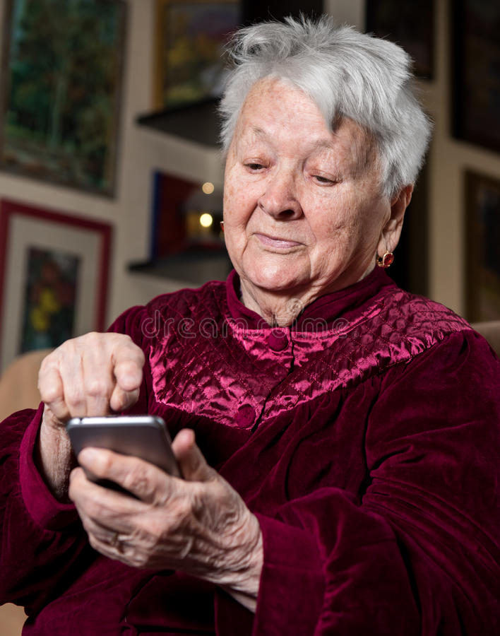 Old woman using smart phone royalty free stock photo