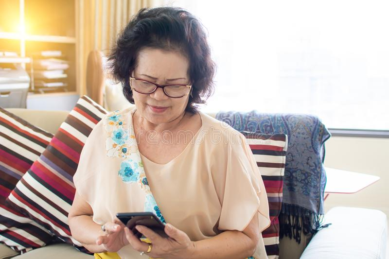 Old woman using technology at home royalty free stock photo