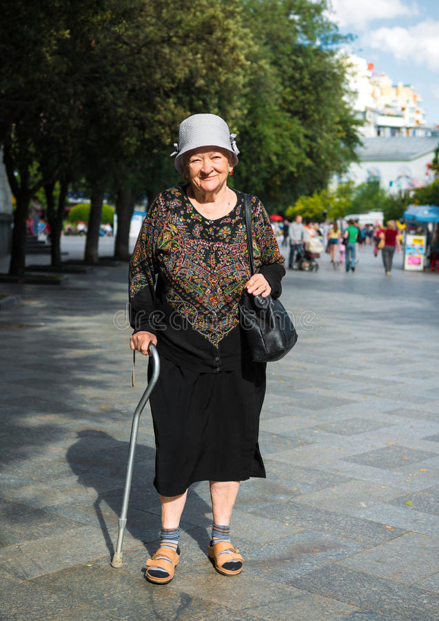Old woman walking with a cane. Down the street of the city royalty free stock images