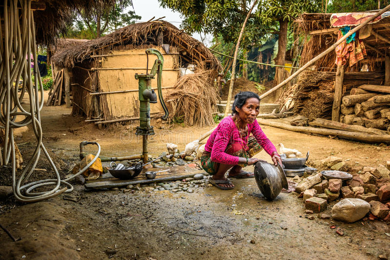 Old woman washing the dishes outside in Nepal royalty free stock photography