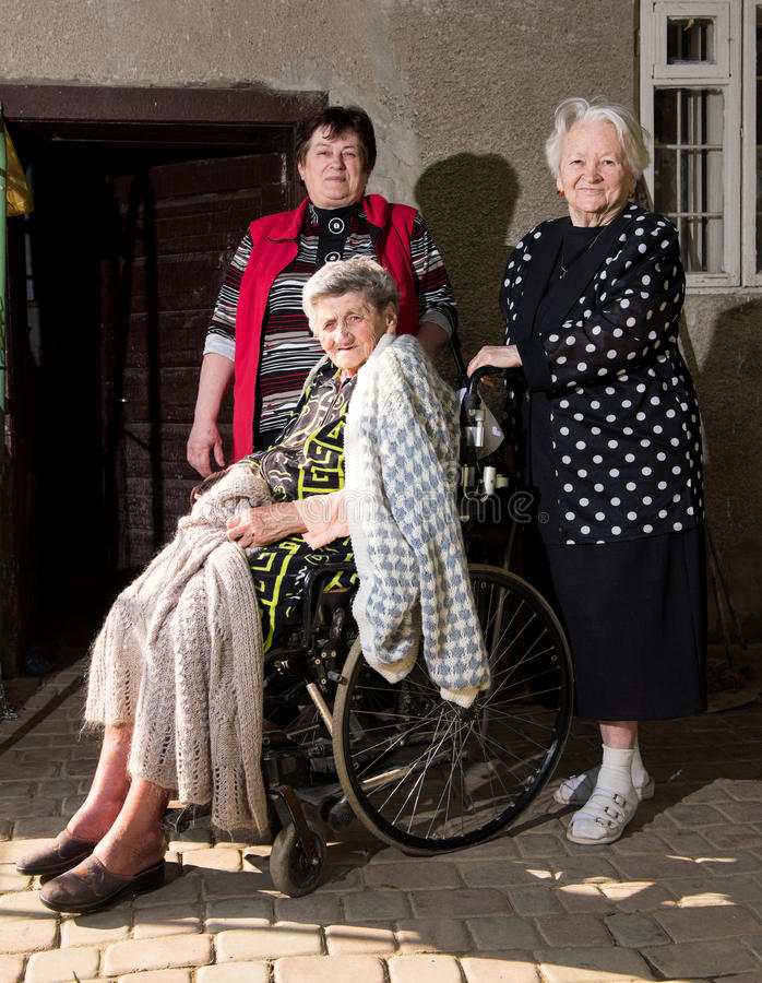 Old woman in wheel chair with family. Old women in wheel chair with daughter and sister outdoors stock photo
