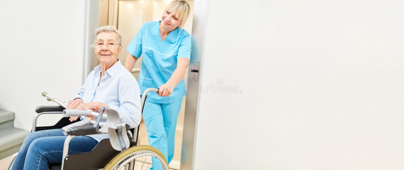 Old woman in wheelchair is being cared for by nurse royalty free stock photos