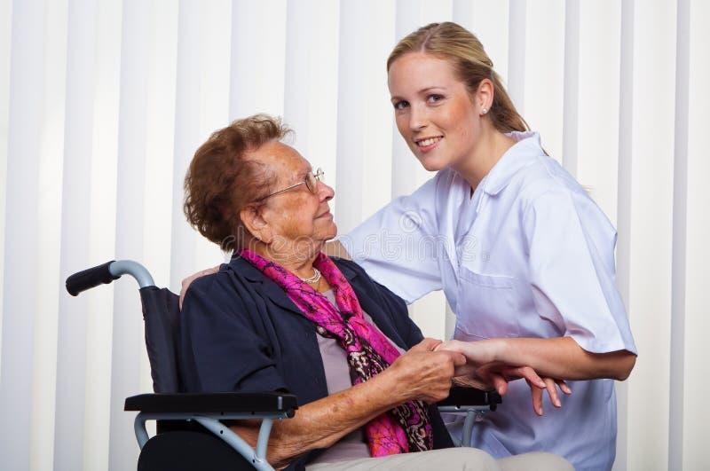 Old woman in a wheelchair and a nurse. A nurse and an old women in a wheelchair stock photography