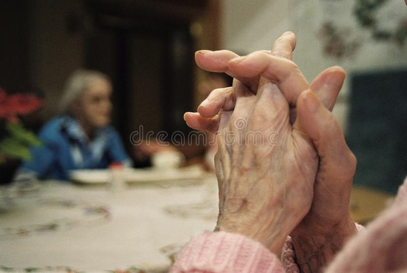 At The Retirement home. An old womans hand praying at The Retirement home stock image