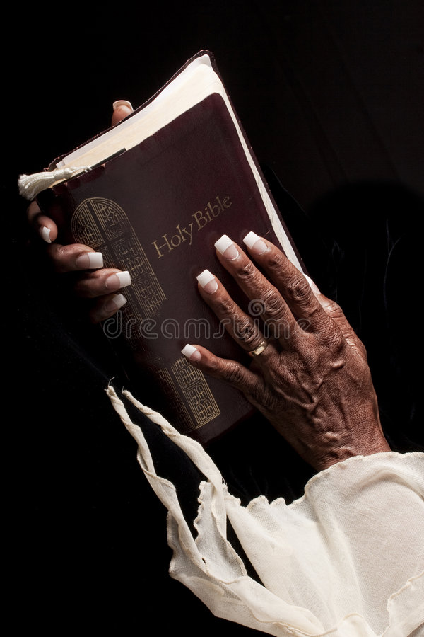 Old womans hands and bible stock photography