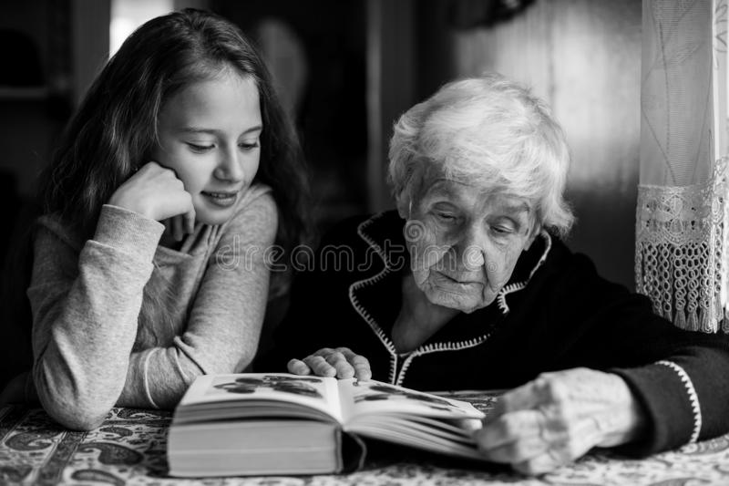 An old woman - a granny with a little girl - granddaughter reading a book. An old women - a granny with a little girl - granddaughter reading a book. Black and royalty free stock photos