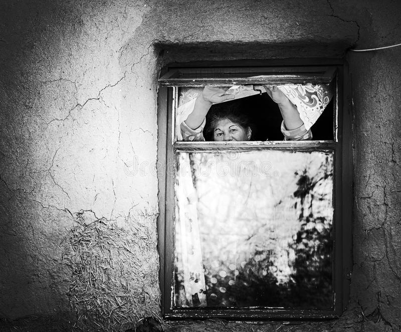 Old women waiting. DUMBRAVENI, CONSTANTA ,ROMANIA - JUNE 2, 2017. Old women waiting, looking outside, over the window in a house of Dobrogea royalty free stock photos