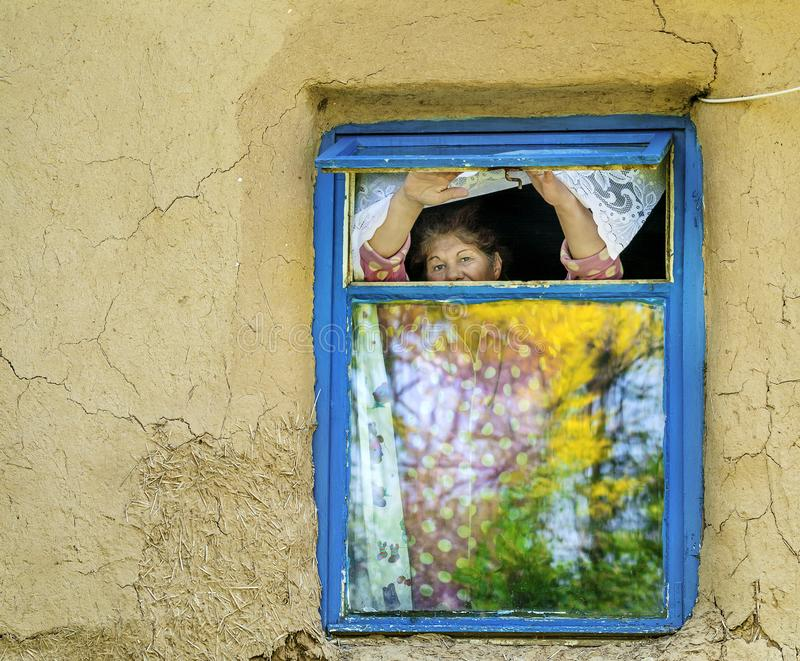 Old women waiting. DUMBRAVENI, CONSTANTA ,ROMANIA - JUNE 2, 2017. Old women waiting, looking outside, over the window in a house of Dobrogea royalty free stock image
