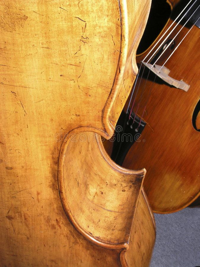 Old Wood. Back, ribs and C bout on double-bass showing texture of wood, violin corners, purfling and blemishes, with another double-bass in background royalty free stock photo