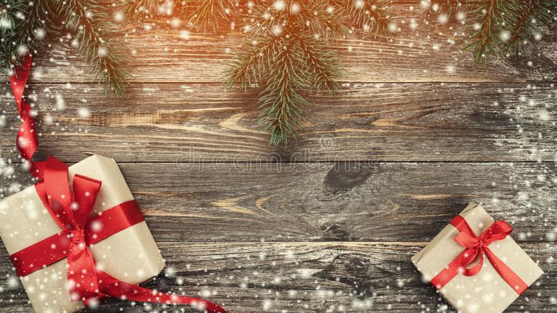 Old wood background with fir branches. Holiday Gifts. Christmas card. Top view. Effect of light and snowflakes.  royalty free stock photo
