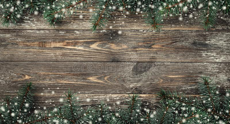 Old wood background with fir branches. Space for a greeting message. Christmas card. Top view. Effect snowflakes.  stock photo