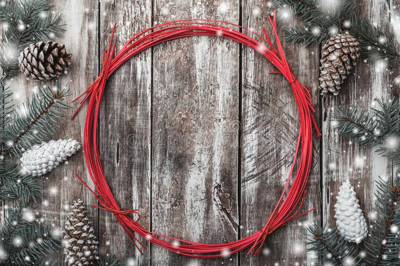 Old wood background, fir cones around a red circle. Holiday space for winter, xmas, New Year and Christmas holidays. Effect of snowflakes. Top view stock photography