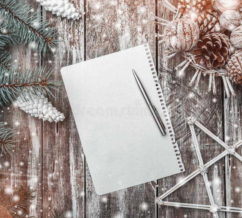 Old wood background, green fir tree with white cones, a basket of cones and walnuts and a decorative star, letter to Santa. stock image