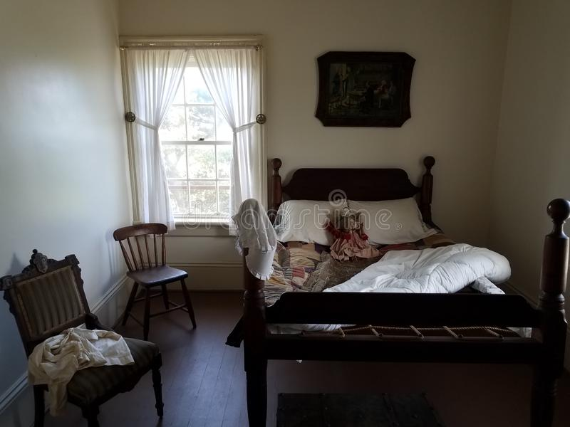 Old wood bed with doll and chairs and window. Old wood bed in room with doll and chairs and window stock photos