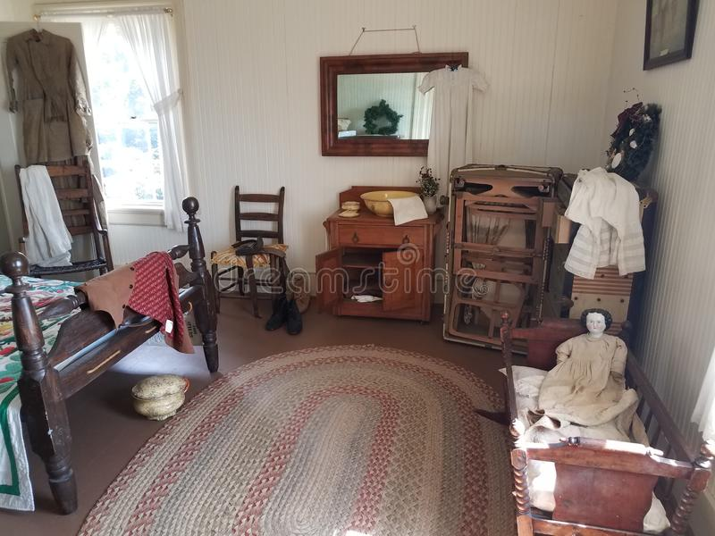 Old wood bed with doll, crib, chamberpot, and chairs and window. Old wood bed in room with crib, doll, chamberpot, and chairs and window stock image