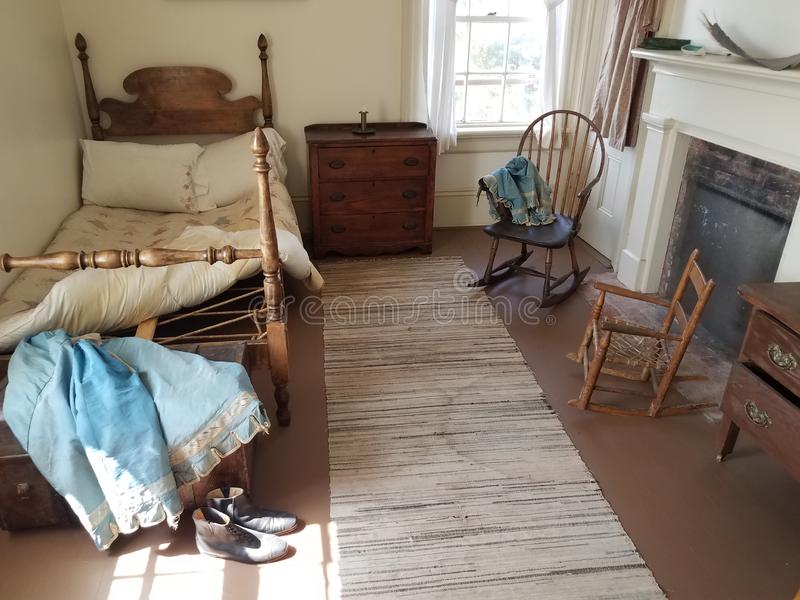 Old wood bed with fireplace and chairs and window. Old wood bed in room with fireplace and chairs and window stock photos