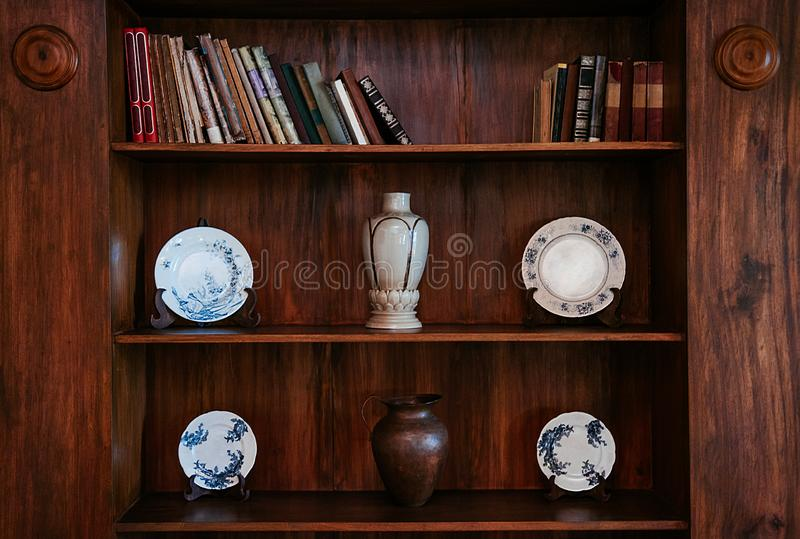 Old wood bookshelf with Chinaware plates, Vase and jar. Wooden bookshelf with old books and blue pattern vintage Chinaware plates, Ceramic Vase and copper jar royalty free stock photography
