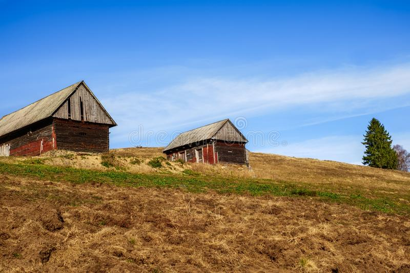 Old wood chalets at the top of the hill. With blue sky stock image