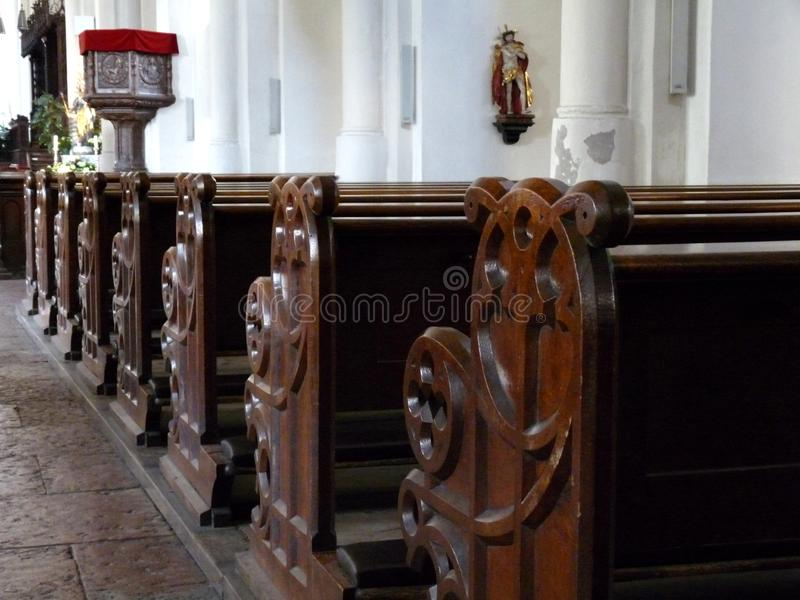 Old wood church bench in historic cathedral. View to old wood church bench in cathedral royalty free stock image