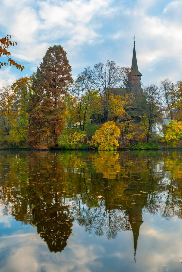 Old wood church reflected in the pond. Tree mirrored in the water on the left royalty free stock photo