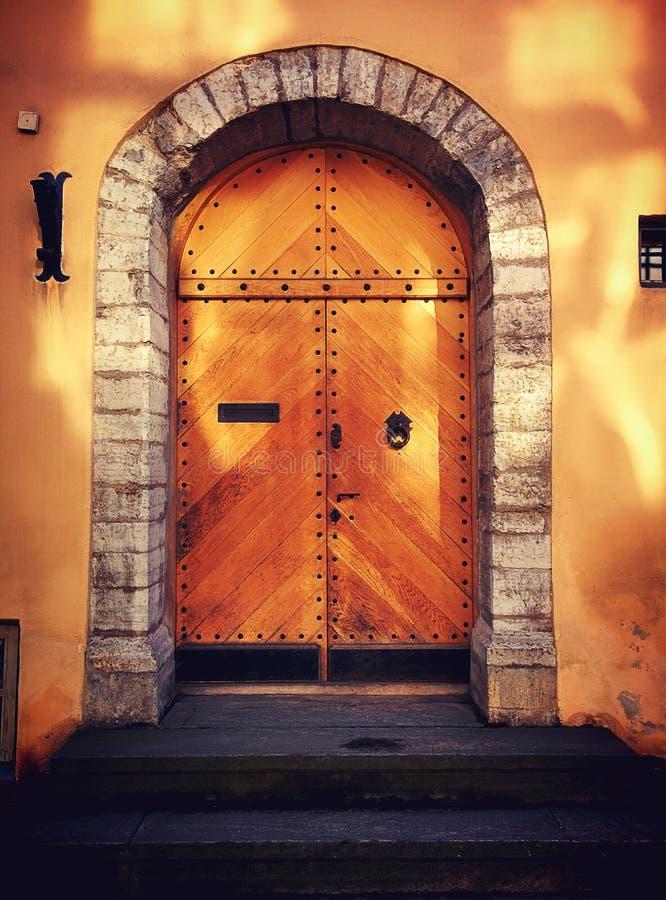 Old wood door with sunlight. In old Tallinn wooden door yellow colour stock photography