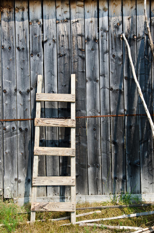 Old Wood Ladder Leaning Over A Grey Wooden Wall Stock