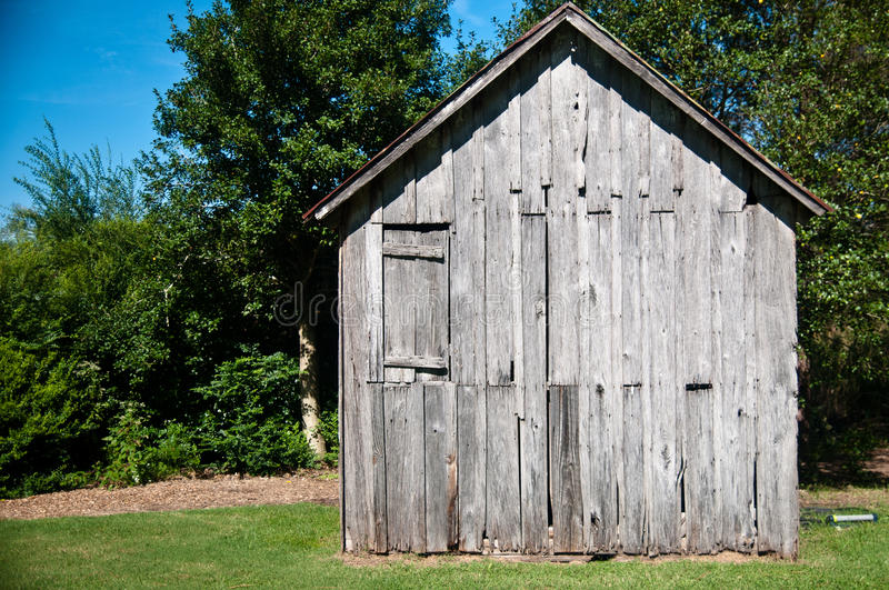 Old Wood Shack. Or cabin in the woods against a beauitful bright blue sky royalty free stock photography