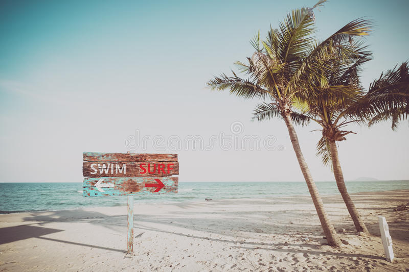 Old wood sign navigate swimming and surfing on a tropical beach in the summer. royalty free stock photography