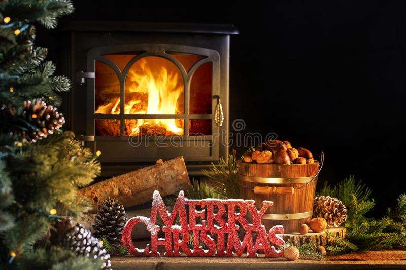 Old Wood Stove Merry Christmas Greeting. Merry Christmas greeting in red snow topped letters on old wood floor with wood burning stove in background and stock photography