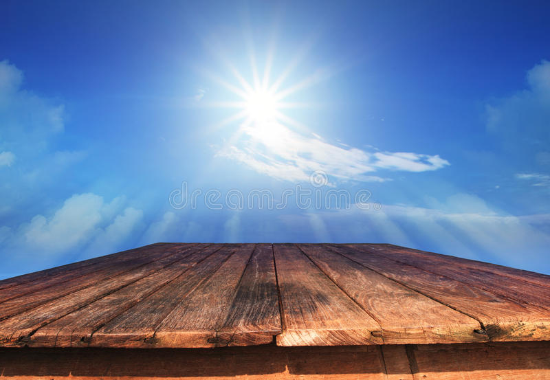 Old wood table and sun shine on blue sky royalty free stock photography