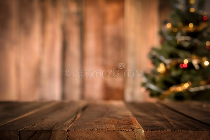 Old wood table top with blur Christmas tree in background royalty free stock image