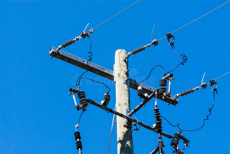 Old wood telephone pole with metal bar and insulators. Old wooden telephone or electrical pole and metal bar with cables and insulators on right side, against royalty free stock photos