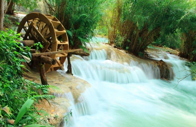 Old wood water turbine on waterfall at Tat Guangxi Waterfall, Luang Prabang. royalty free stock image