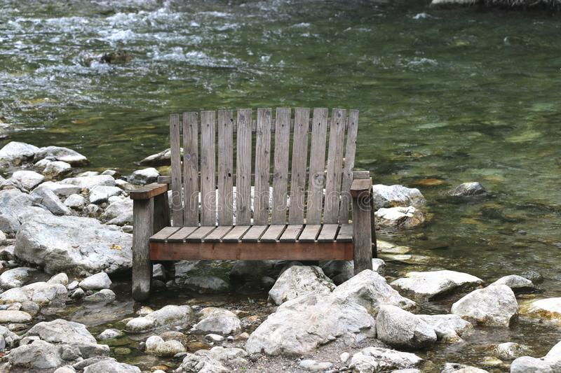 Old wooden adirondack bench in a river bed, Big Sur, CA. royalty free stock photos